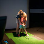 Image of mother holding daughter showing her how to swing a club
