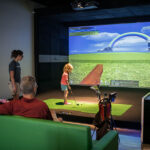 Image of little girl about to hit the ball at a fantasy X-Golf course