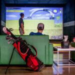 Image of man watching woman hit at X-Golf simulator bay