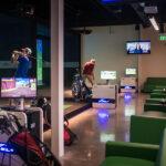 Image of several people hitting at X-Golf simulator bays
