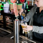 Image of woman bartender pouring cold beer at X-Golf