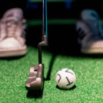 Close up image of an X-Golf ball about to be Putted