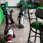 Image of two golf bags among green furniture