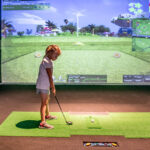 Image of little girl standing near the ball at X-Golf